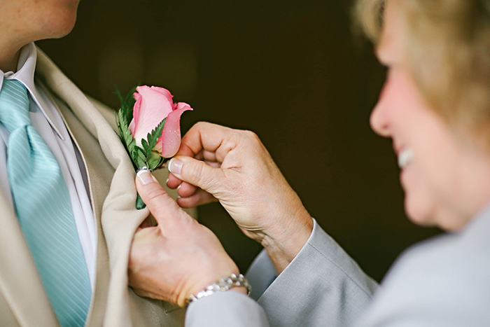 mother pinning pink rose to groom's lapel