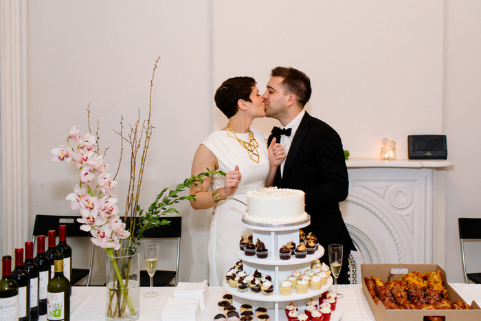 bride and groom kissing in front of cake