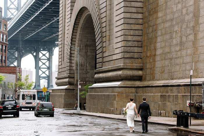 bride and groom walking by brooklyn bridge