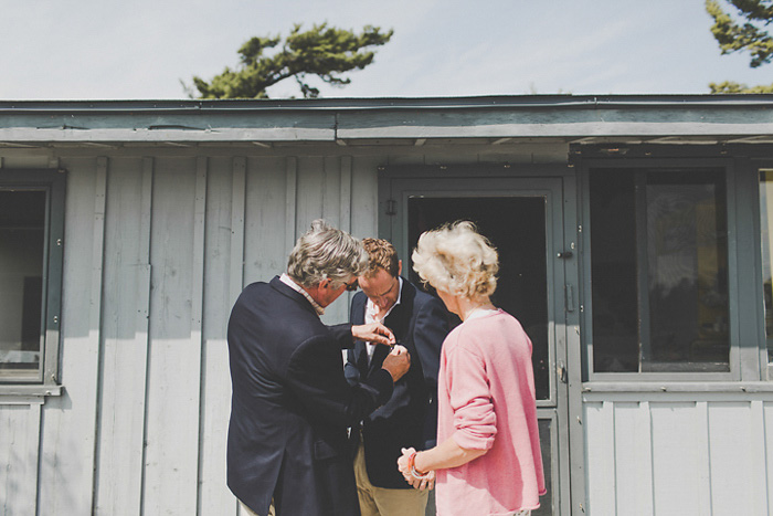 parents pinning boutonniere on groom
