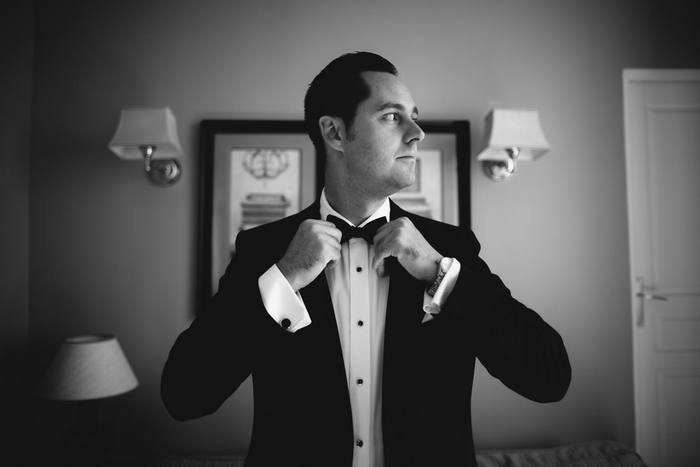 groom adjusting bow tie