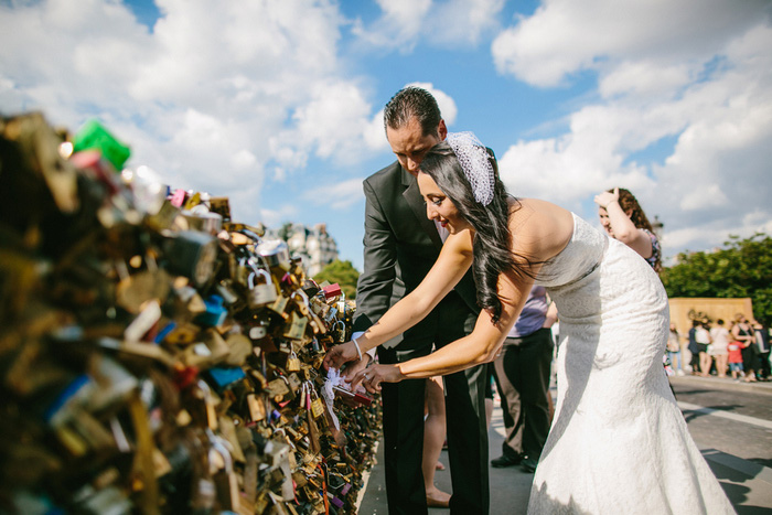 bride and groom adding lock to Paris bridge