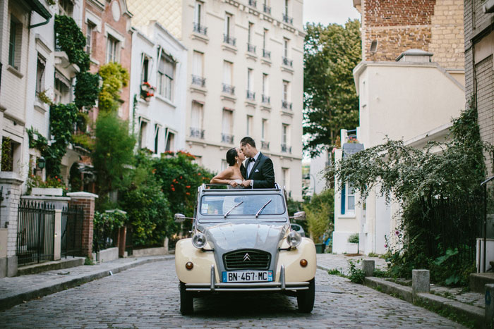 bride and groom kissing while standing in VW bug