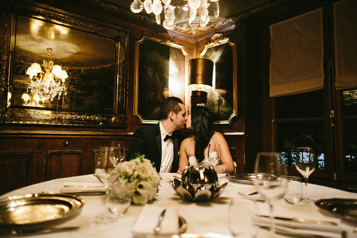 brideand groom kissing in Paris restautrant