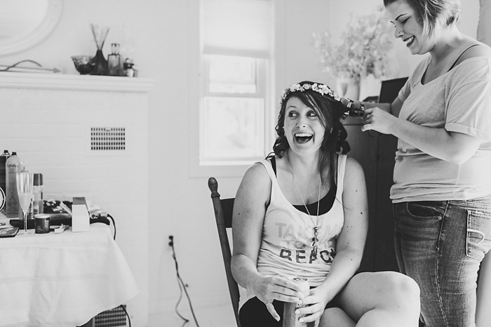 bride laughing while getting her hair done