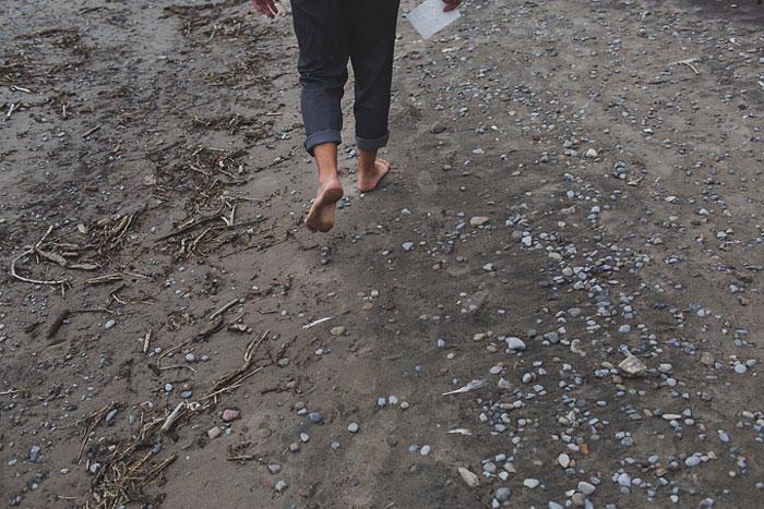 groom walking on the beach