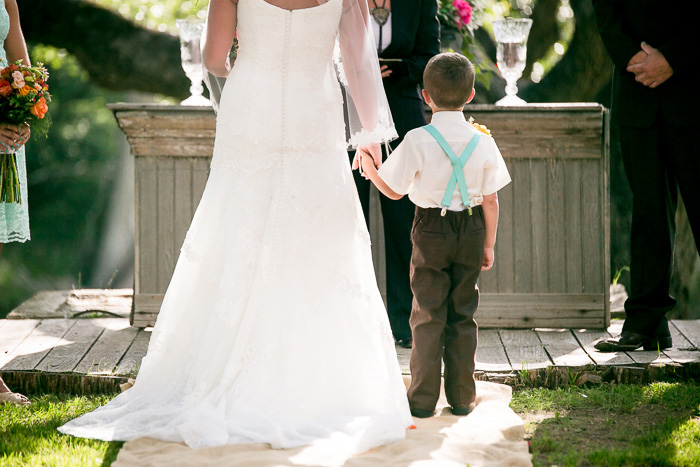 bride holding son's hand at wedding ceremony
