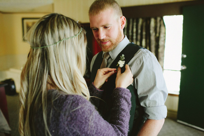 bride pinning boutonniere on groom
