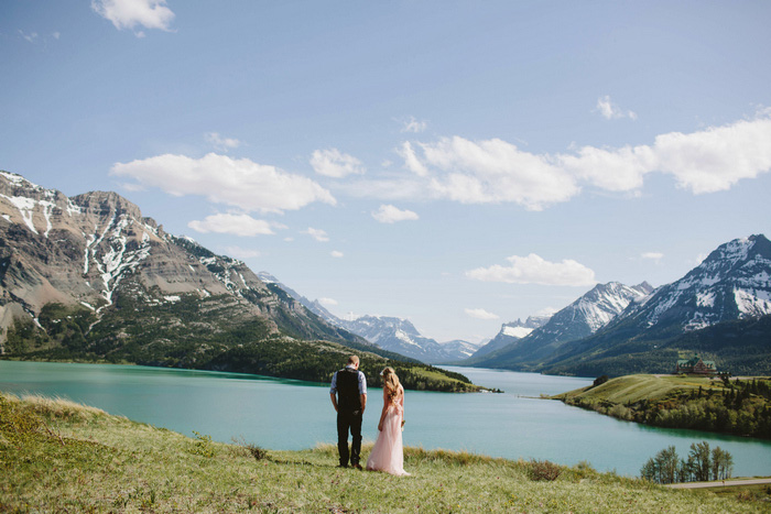 bride and groom by lake and mountains