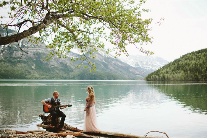 groom serenading bride by the lake
