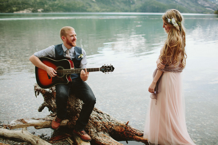 groom playing guitar by the lake