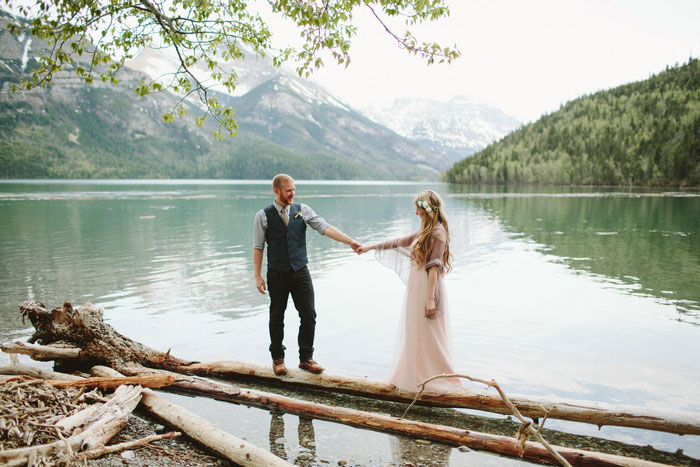 bride and groom walking across logs