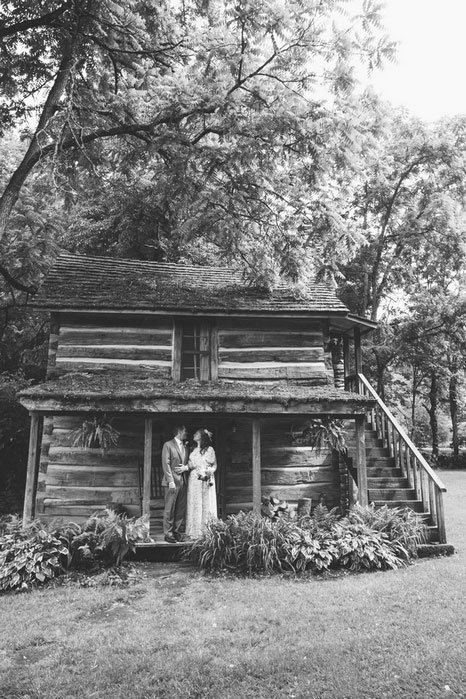 bride and groom standing on cabin porch