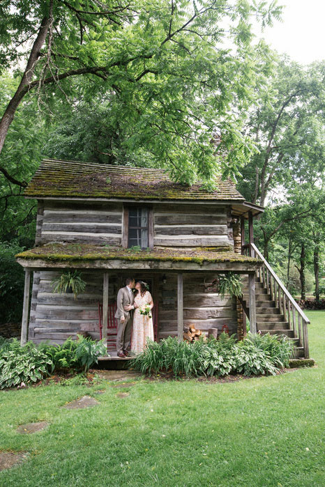 bride and groom kissing on cabin porch