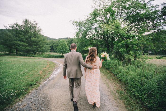 bride and groom walking down dirt road