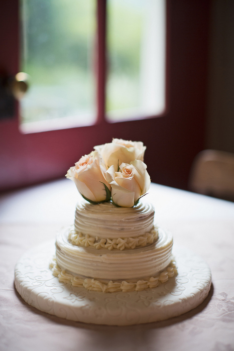 small wedding cake with roses on top