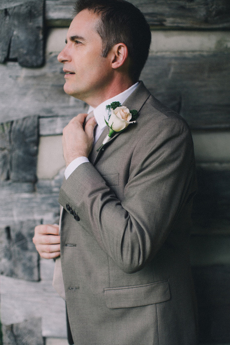 groom adjusting tie