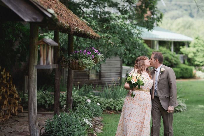 bride and groom kissing on farm grounds