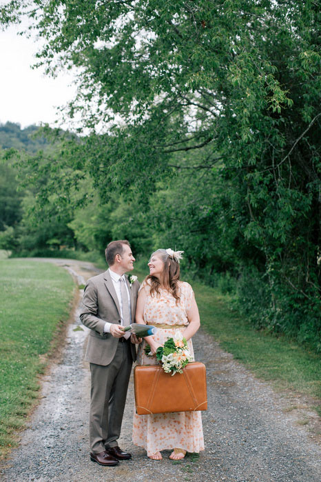 bride and groom portrait with suitcase