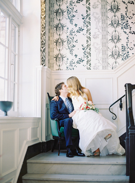 bride and groom kissing in chair