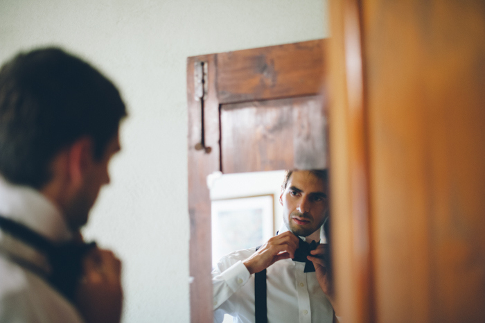 groom tying his bow tie