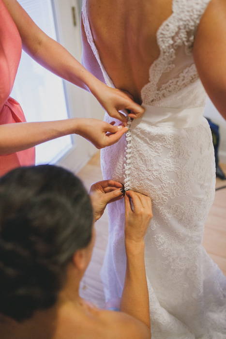 bride getting her dress buttoned up