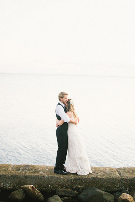 bride and groom hugging by the ocean