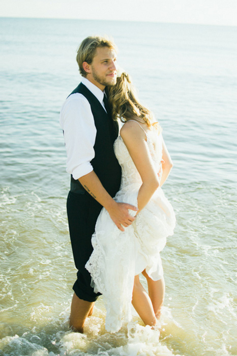 bride and groom wading in the water