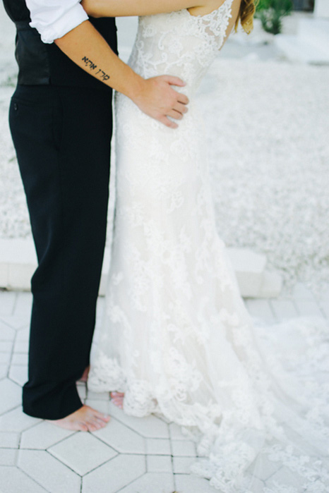 close-up of groom's hands on bride's hips