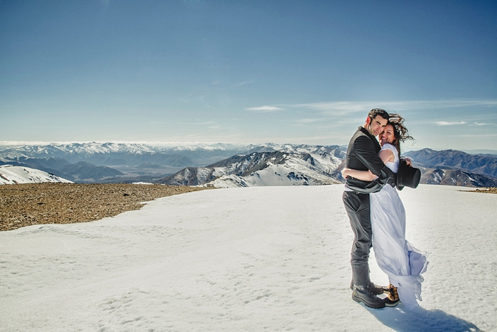 bride and groom hugging on windy mountain top