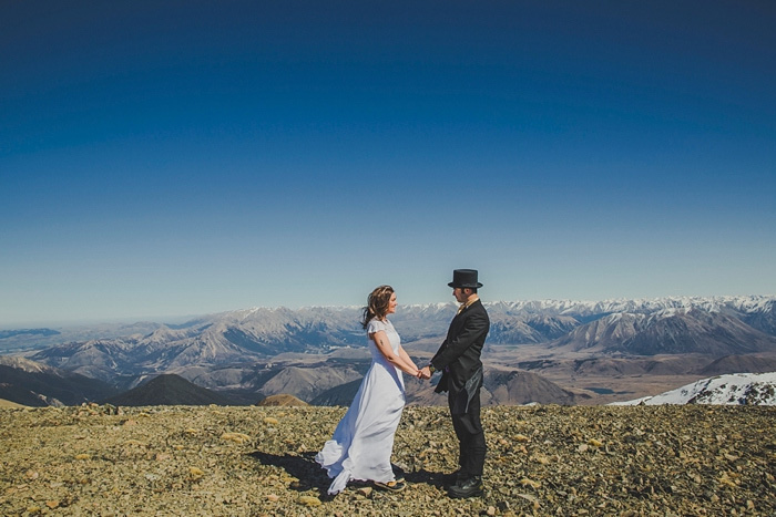 bride and groom holding hands onmountain