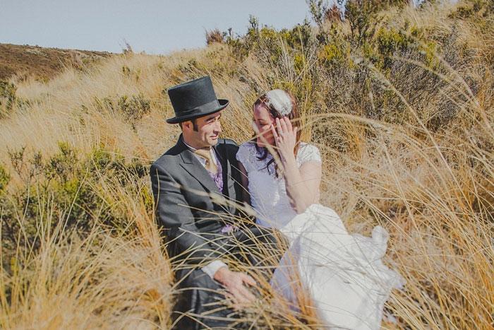 bride and groom sitting in field