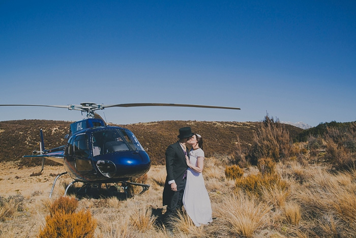 bride and groom kissing by helicopter