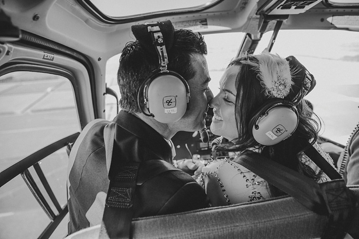 bride and groom kissing in helicopter