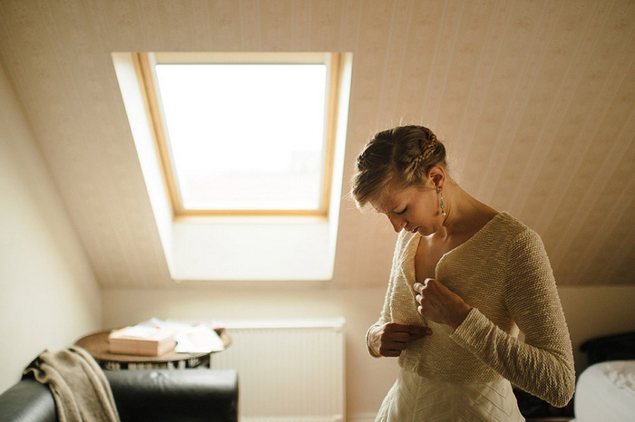 bride buttoning sweater