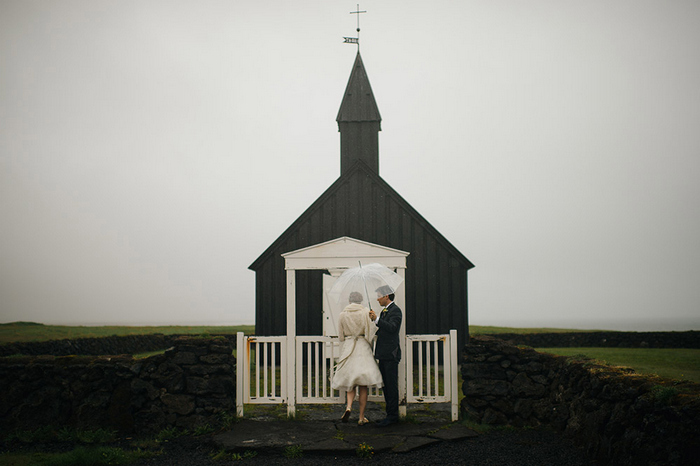 bride and groom in front of black chapel