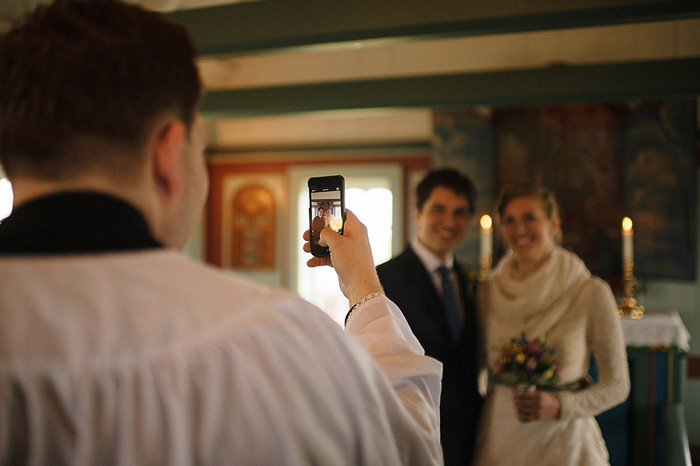 officiant taking phone photo of bride and groom