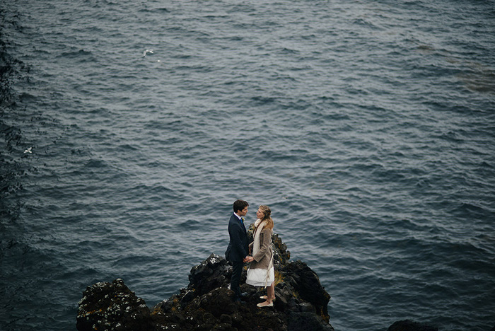bride and groom standing by ocean