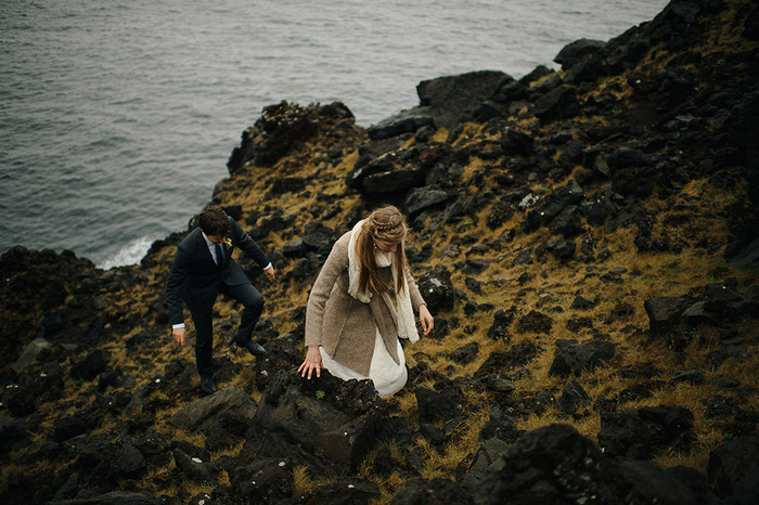 bride and groom climbing rocks