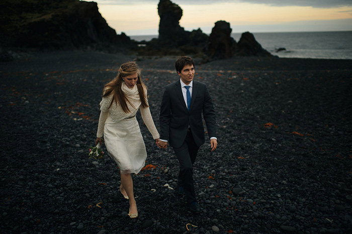 bride and groom walking on black rock beach