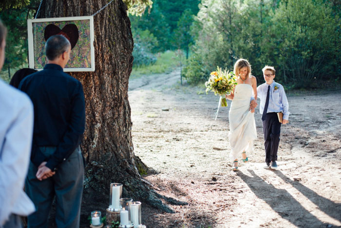 bride walking down aisle with son