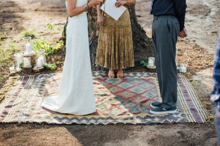 bride and groom standing on rug in outdoor ceremony