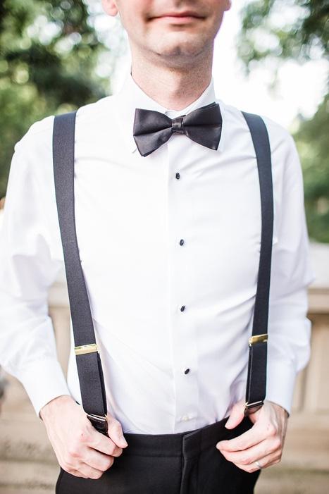 groom in suspenders and black bow tie