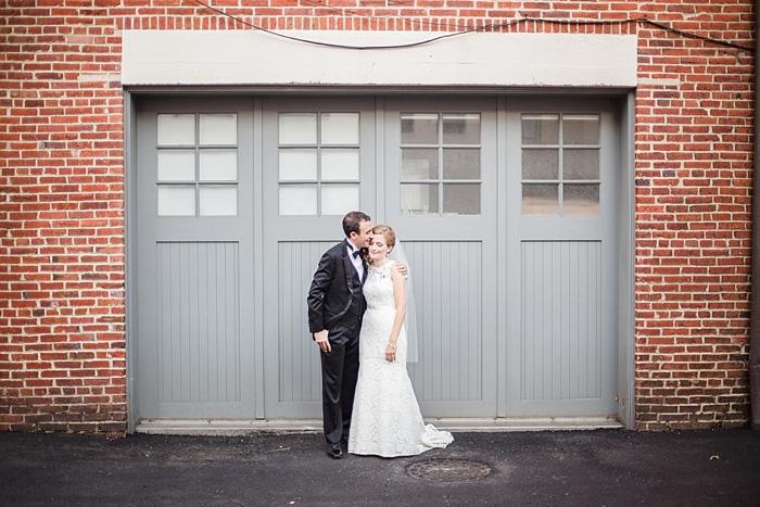 bride and groom in front of grey garage doors