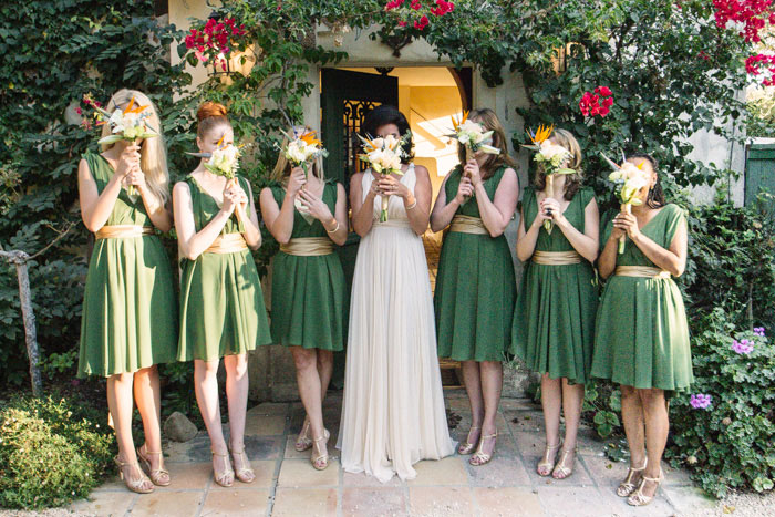 bridal party holding bouquets in front of faces