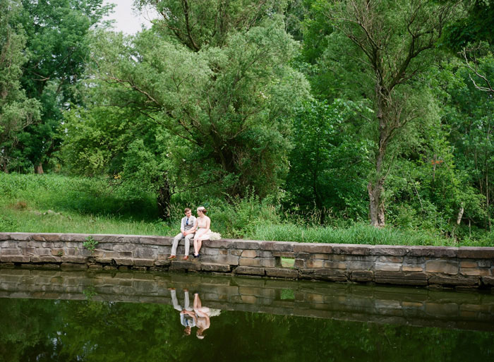 bride and groom sitting at edge of pond