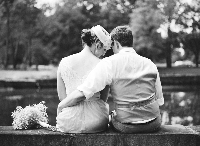 bride and groom sitting by pond