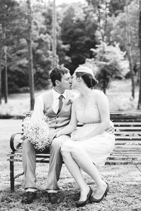 bride and groom kissing on bench