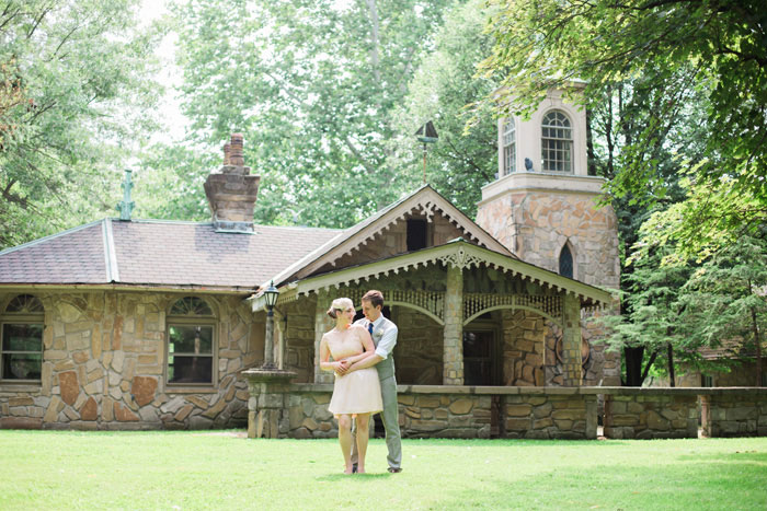 bride and groom in front of stone cottage