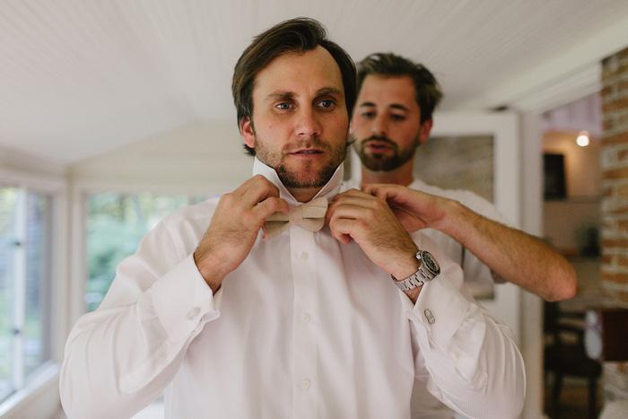 groom tying bow tie